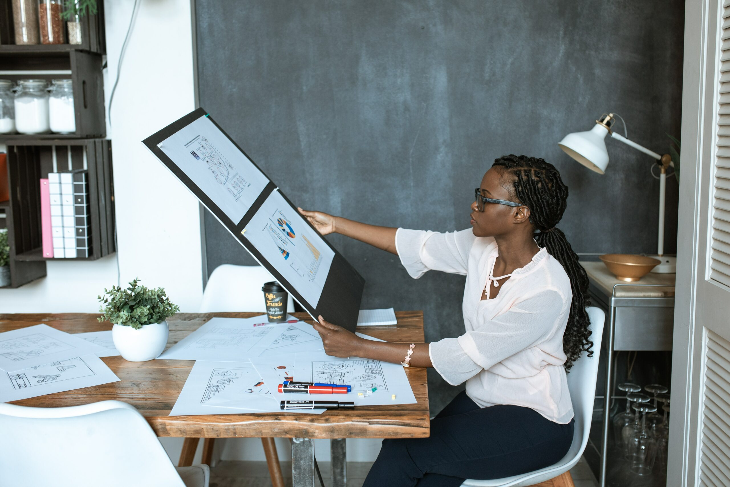 Woman sitting at a desk reviewing artwork which tells a story in a visual way