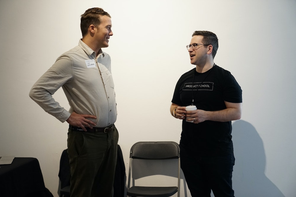 Two men speaking at a conference. Meeting other conference participants and attending your colleagues' presentations can help make your own presentation less nerve-wracking.